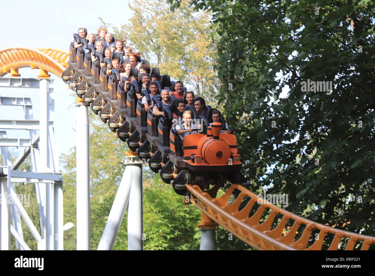 Swiftly descending down rollercoaster rail train with peoples. Amusement park Divo-island. Saint-Petersburg. - Stock Image