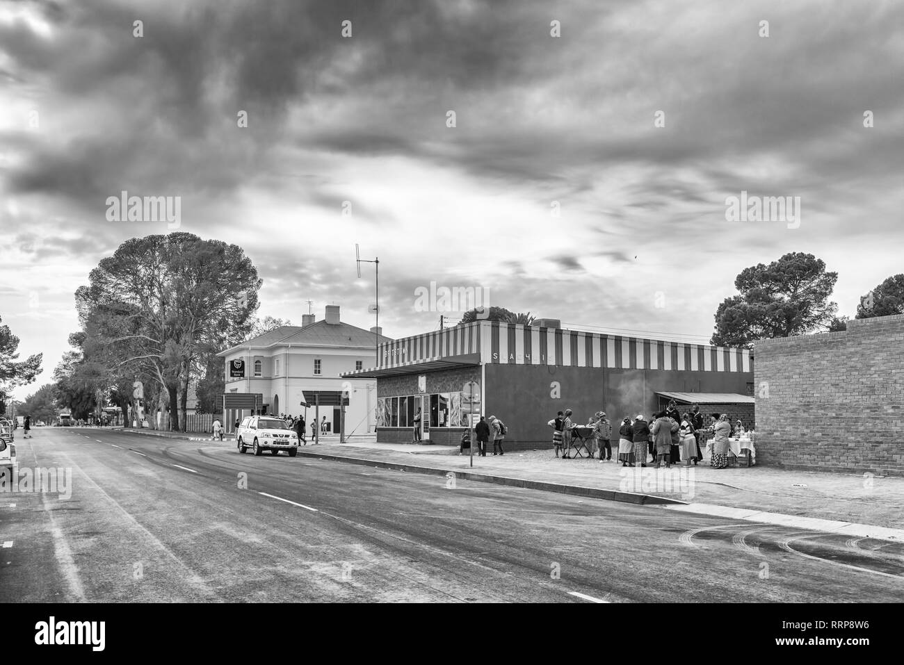 BRITSTOWN, SOUTH AFRICA, SEPTEMBER 1, 2018: A street scene, with businesses, people and vehicles, in Britstown in the Northern Cape Province. Monochro - Stock Image
