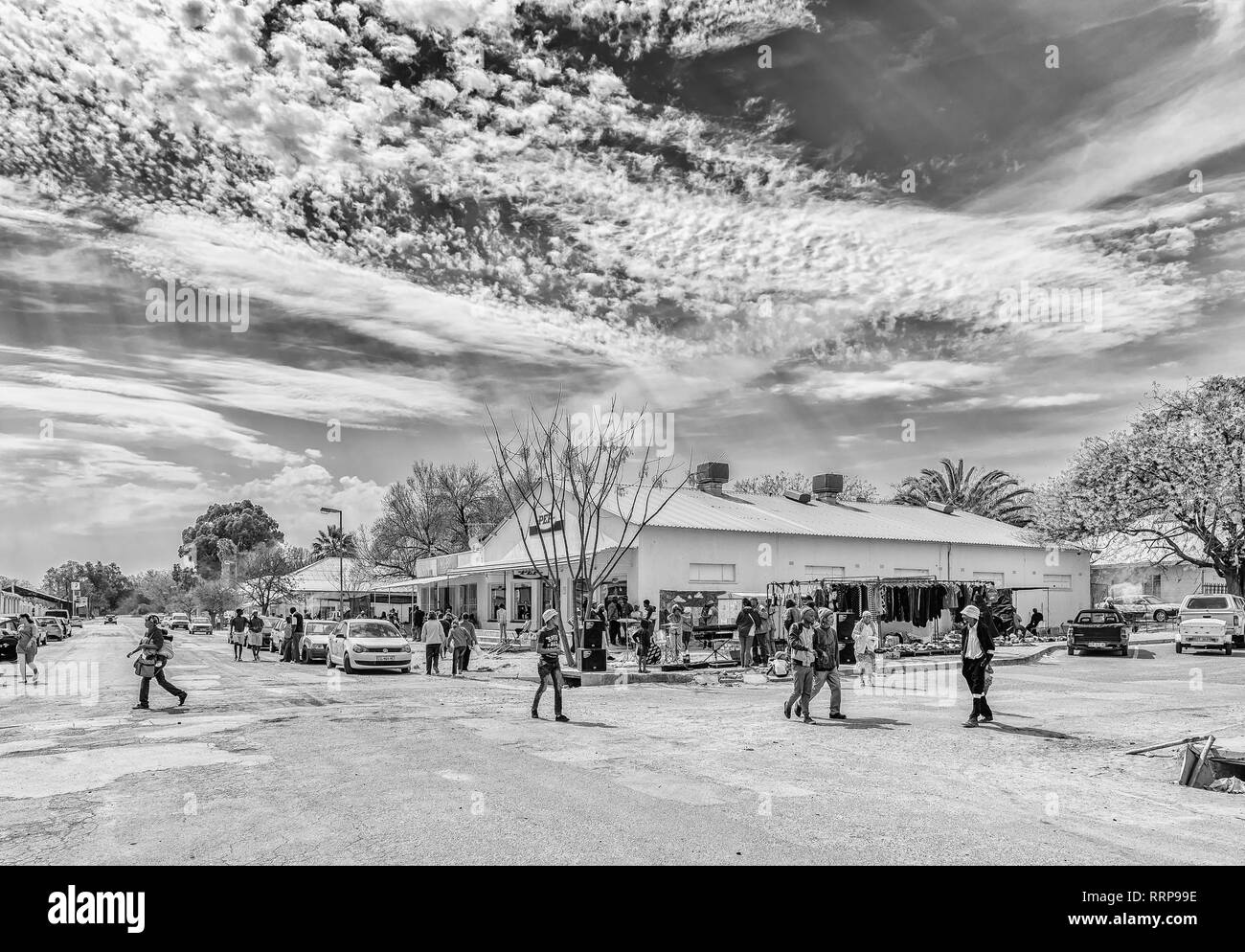 HOPETOWN, SOUTH AFRICA, SEPTEMBER 1, 2018: A street scene, with a businesses, vehicles and people, in Hopetown in the Northern Cape Province. Monochro - Stock Image