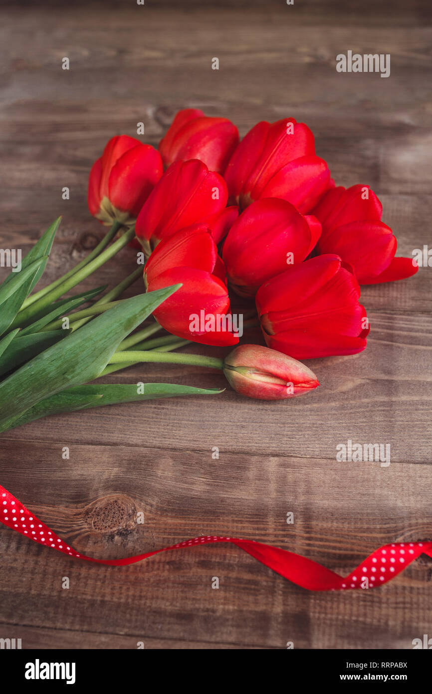 Spring flowers. Bouquet of Red tulips on brown wooden background. Mother's Day and Valentines Day background - Stock Image