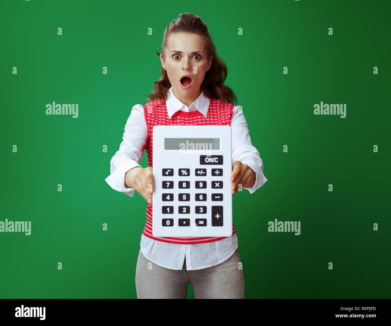 shocked fit student in grey jeans and pink sleeveless shirt showing big white calculator isolated on chalkboard green. Financial challenges and expend Stock Photo