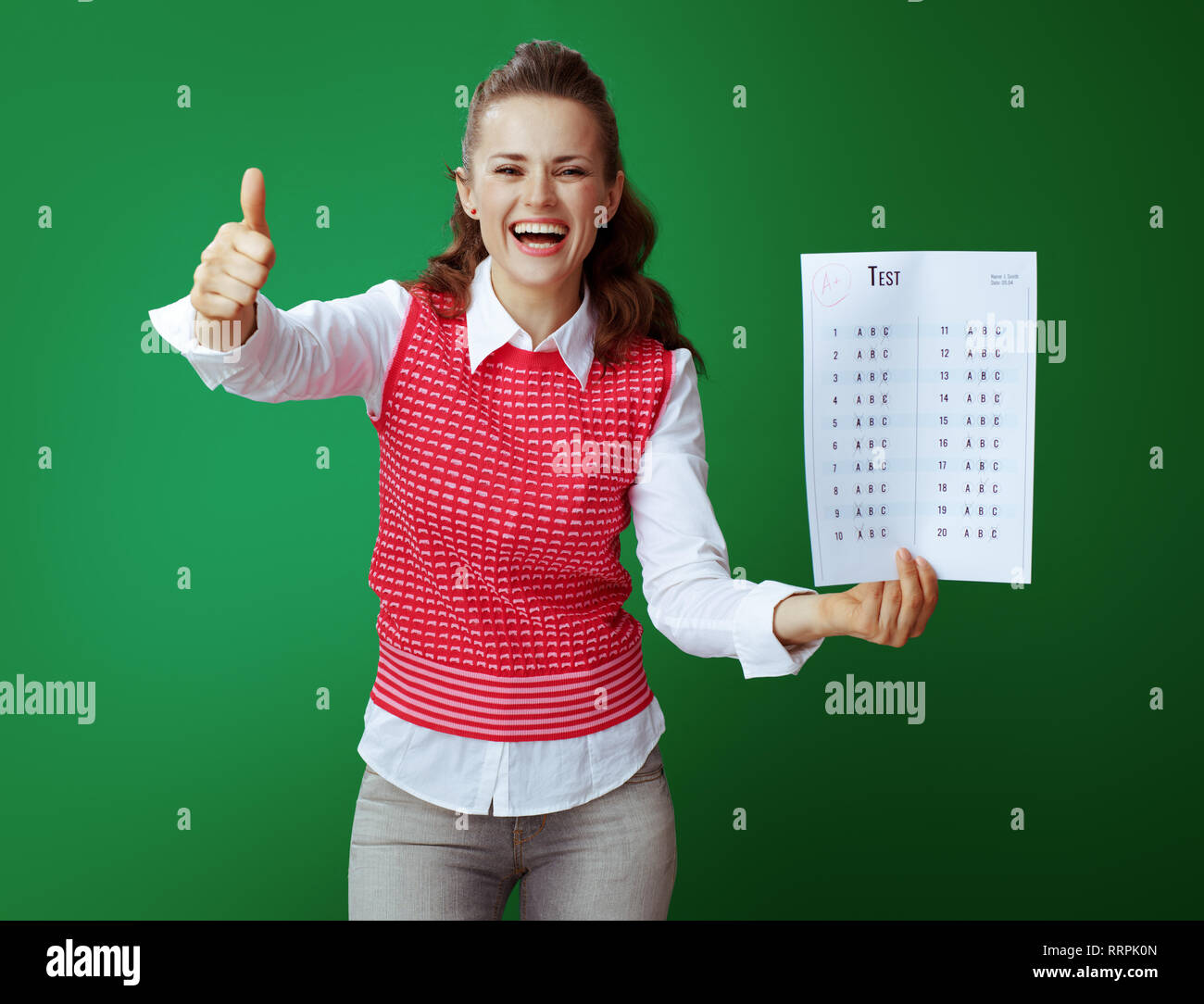 smiling young student in grey jeans and pink sleeveless shirt showing A+ exam result against green background. - Stock Image