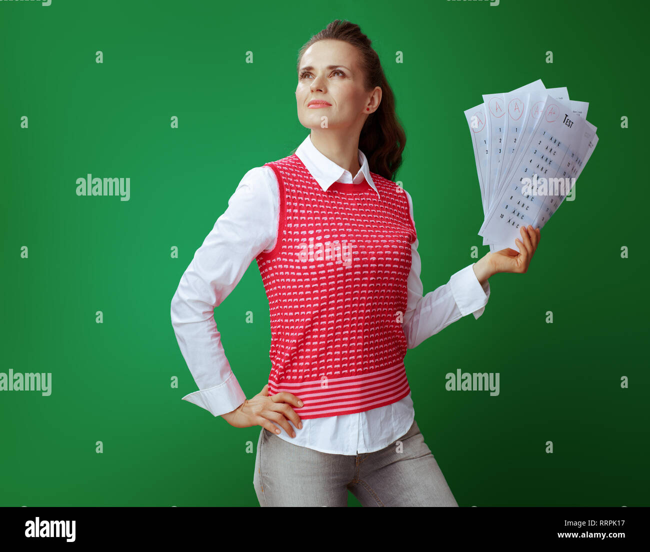 proud healthy student woman in grey jeans and pink sleeveless shirt showing A+ exam results against green background. - Stock Image