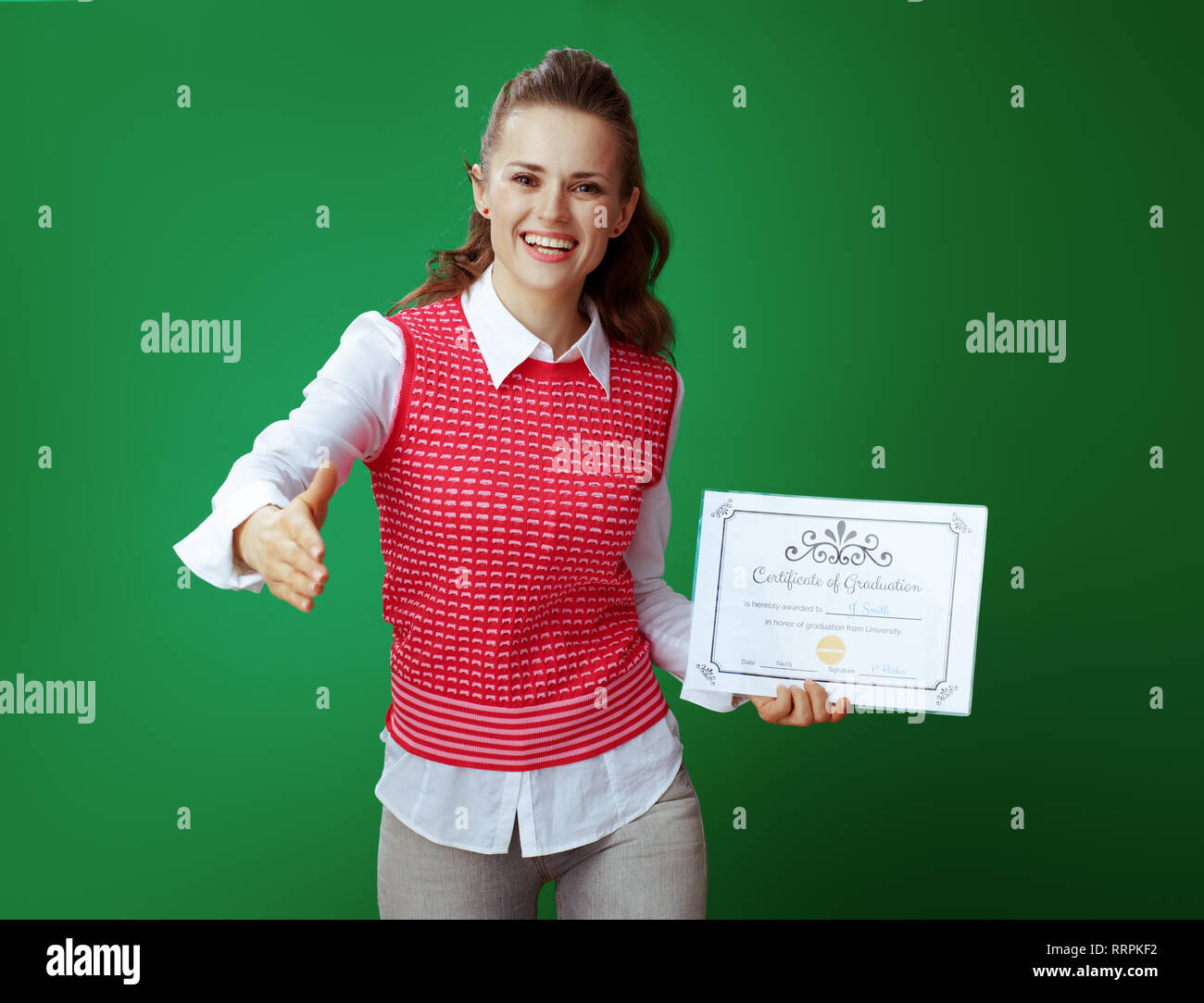 happy fit learner woman in grey jeans and pink sleeveless shirt with Certificate of Graduation giving hand for a handshake isolated on chalkboard gree - Stock Image