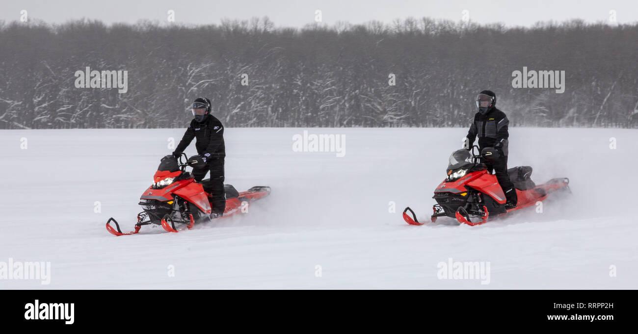 Eben Junction, Michigan - Snowmobiles race across a snow-covered farm field in Michigan's upper peninsula. - Stock Image