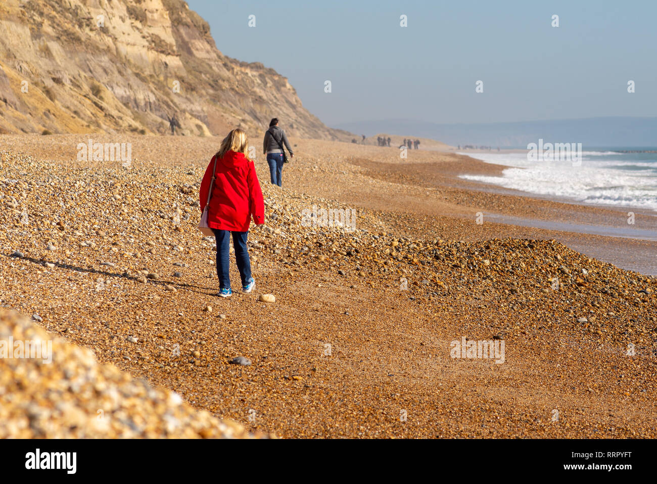 Hengistbury Head, Christchurch, Dorset, UK, 26th February 2019, Weather: People walk along the pebbly beach of the coastal spit this afternoon in unusually high temperatures for February. Even with an onshore breeze, with warm air coming up from the south, 15 degrees centigrade has been reached in this record breaking spell of winter weather for the UK. Credit: Paul Biggins/Alamy Live News - Stock Image