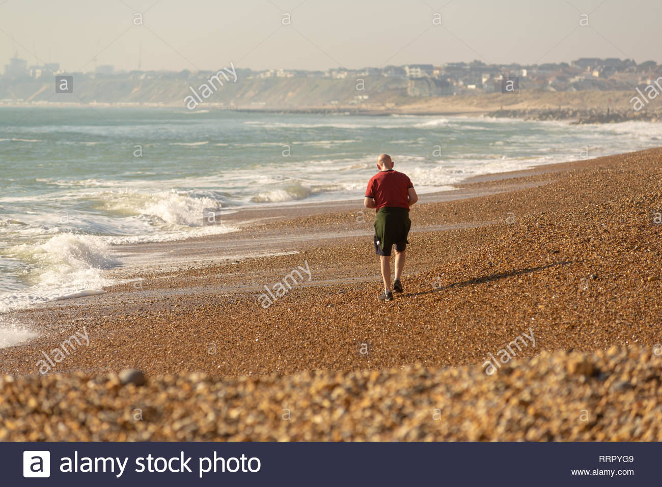 Hengistbury Head, Christchurch, Dorset, UK, 26th February 2019, Weather: A man in t-shirt and shorts walks along the pebbly beach of the coastal spit this afternoon in unusually high temperatures for February. Even with an onshore breeze, with warm air coming up from the south, 15 degrees centigrade has been reached in this record breaking spell of winter weather for the UK. Credit: Paul Biggins/Alamy Live News - Stock Image