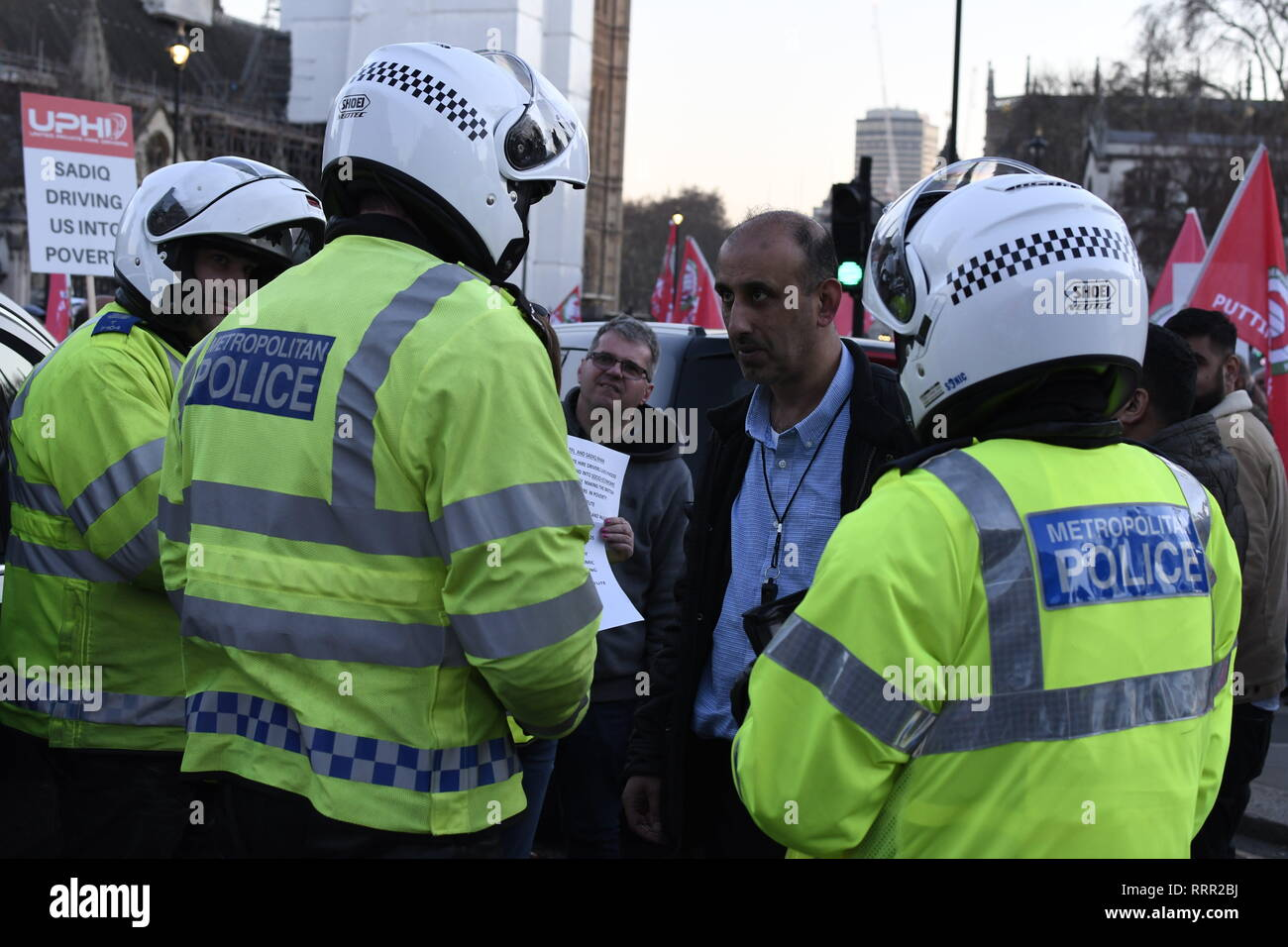 London, Greater London, UK. 25th Feb, 2019. Police officers seen talking to a demonstrator during the protest.Minicab drivers blocked Parliament Square in protest over changes to the congestion charge. Drivers are against congestion charges introduced by Mayor Sadiq Khan. TFL said the measure is necessary to reduce London's air pollution. Credit: Andres Pantoja/SOPA Images/ZUMA Wire/Alamy Live News - Stock Image