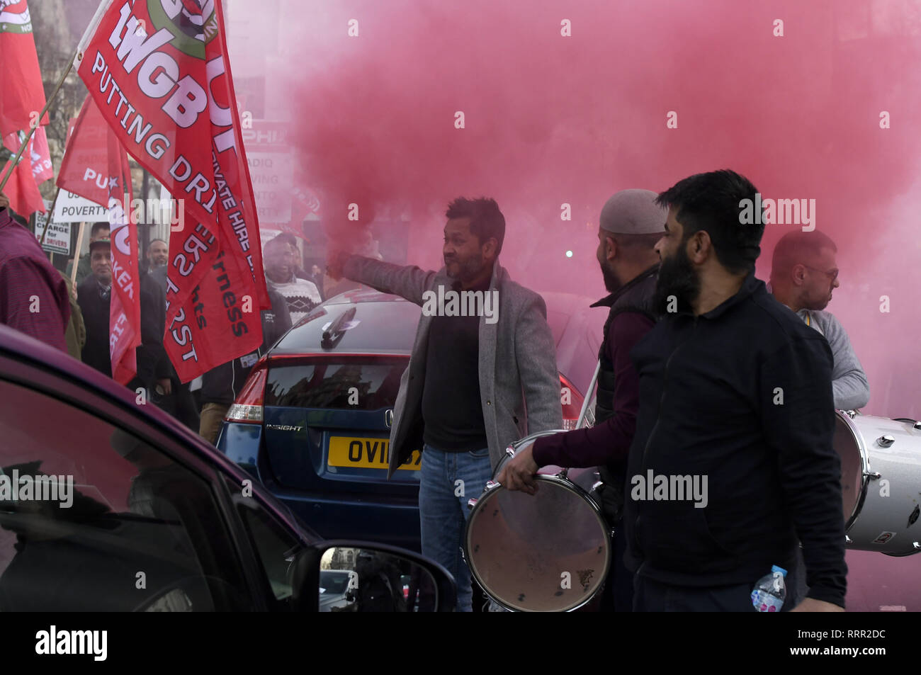 London, Greater London, UK. 25th Feb, 2019. Minicab drivers seen under coloured gas during the protest.Minicab drivers blocked Parliament Square in protest over changes to the congestion charge. Drivers are against congestion charges introduced by Mayor Sadiq Khan. TFL said the measure is necessary to reduce London's air pollution. Credit: Andres Pantoja/SOPA Images/ZUMA Wire/Alamy Live News - Stock Image