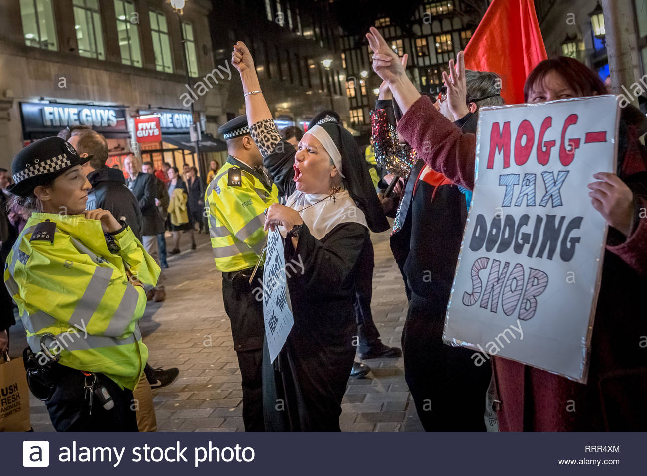London, UK. 26th February 2019. Protesters from Class War anarchist group hold a lively demonstration outside the London Palladium theatre against the scheduled evening talk with Conservative MP Jacob Rees-Mogg. Class War members including long time anarchist, Ian Bone and Jane Nicholl (dressed as a nun), claim Rees-Mogg is a religious extremist referencing his outspoken views on abortion. Credit: Guy Corbishley Credit: Guy Corbishley/Alamy Live News - Stock Image