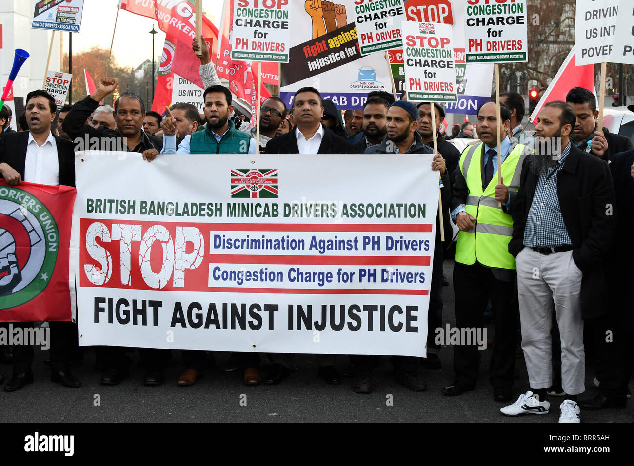 Minicab drivers seen holding a banner during the protest. Minicab drivers blocked Parliament Square in protest over changes to the congestion charge. Drivers are against congestion charges introduced by Mayor Sadiq Khan. TFL said the measure is necessary to reduce London's air pollution. - Stock Image
