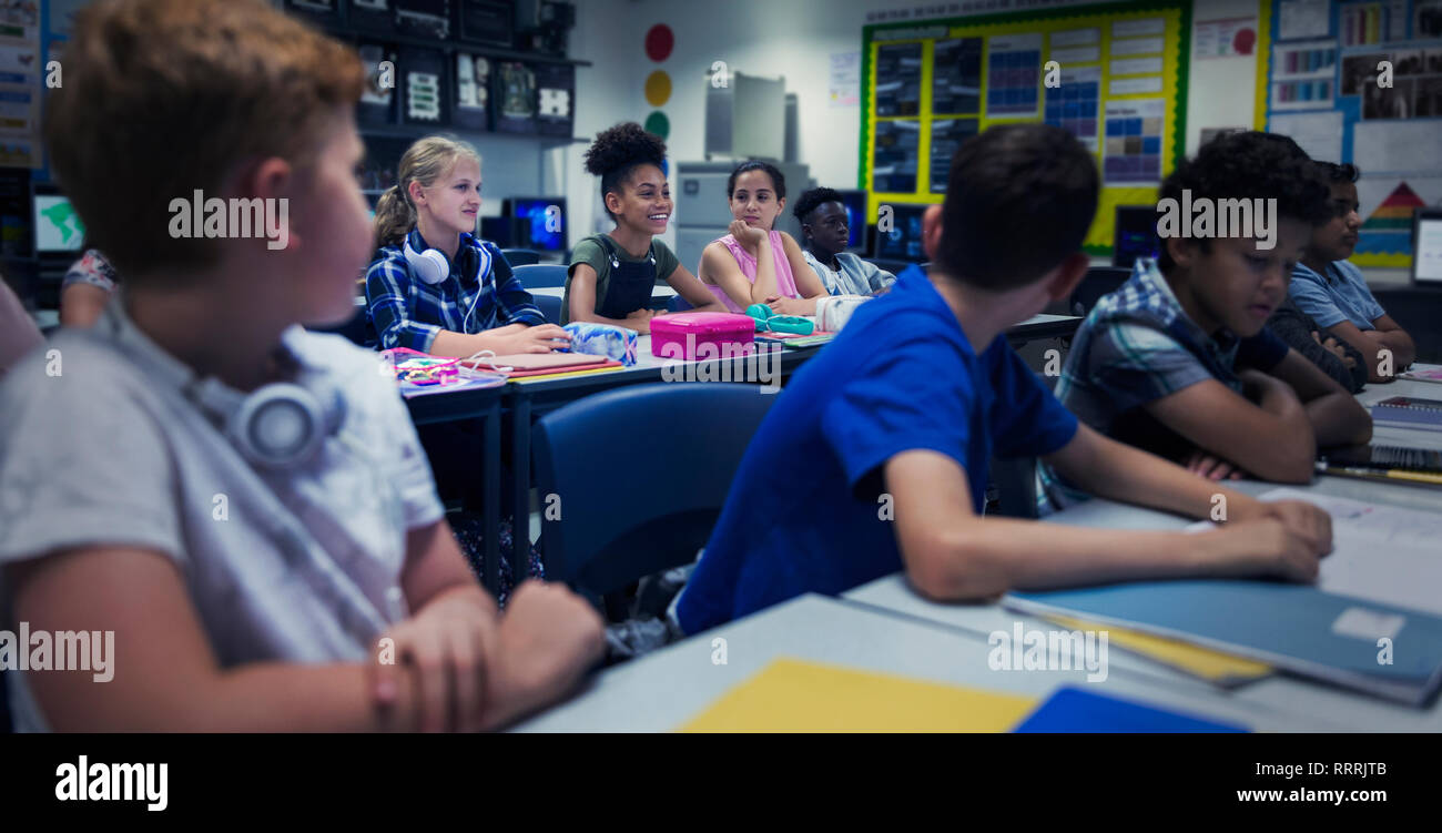 Junior high school students at desks in classroom - Stock Image