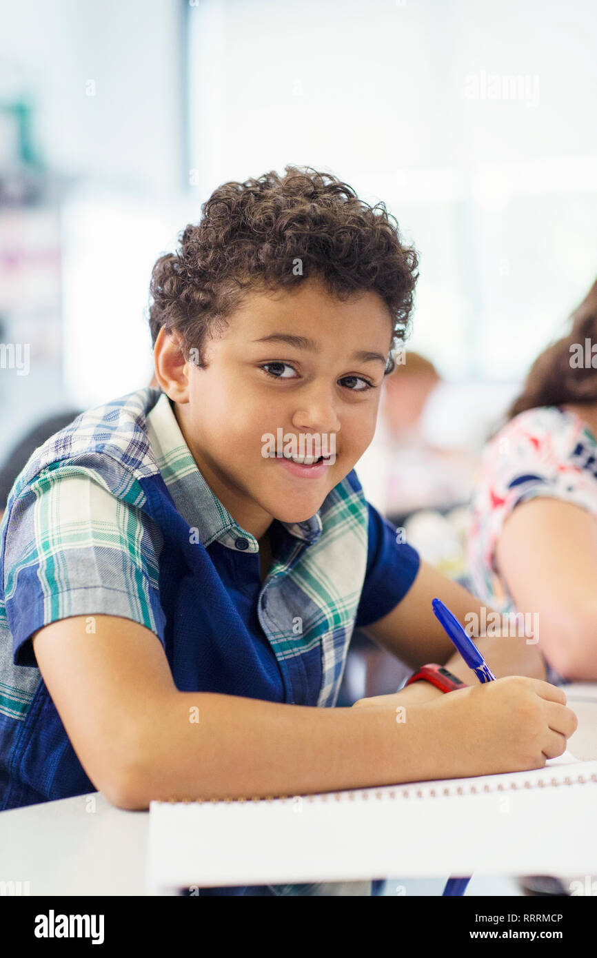 Portrait confident elementary age boy doing homework in classroom - Stock Image