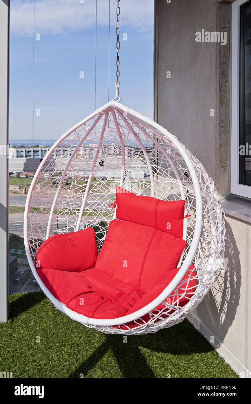 View Of A Modern Cozy Hanging Chair With Red Pillows On A