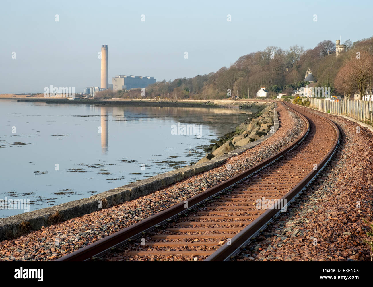 The Kincardine railway line at Culross, Fife with the former Longannet power station in the distance. - Stock Image