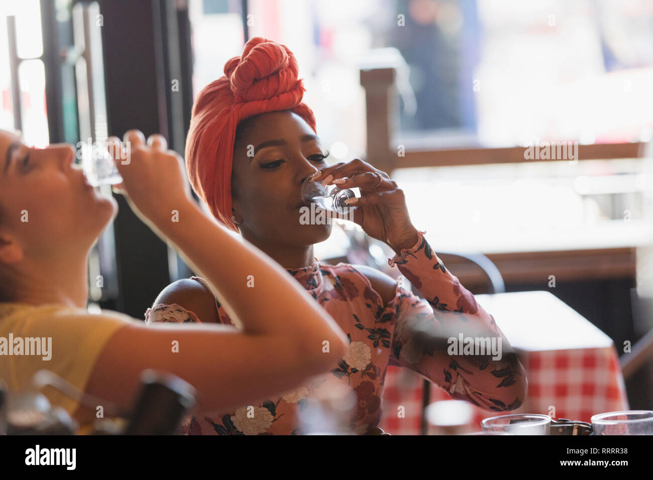 Young women friends taking alcohol shots in bar - Stock Image