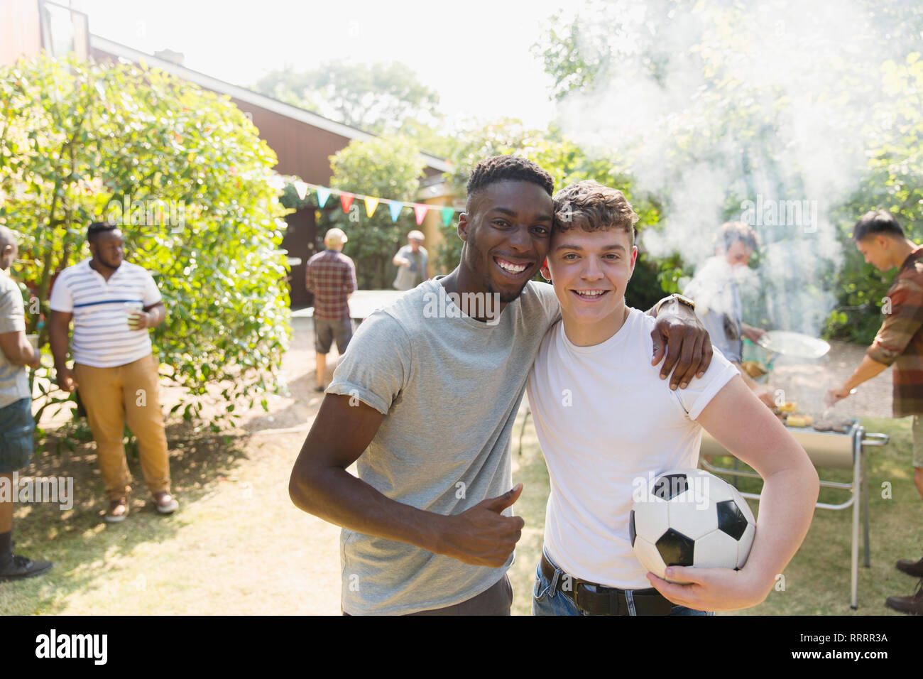 Portrait confident young men with soccer ball enjoying backyard barbecue Stock Photo