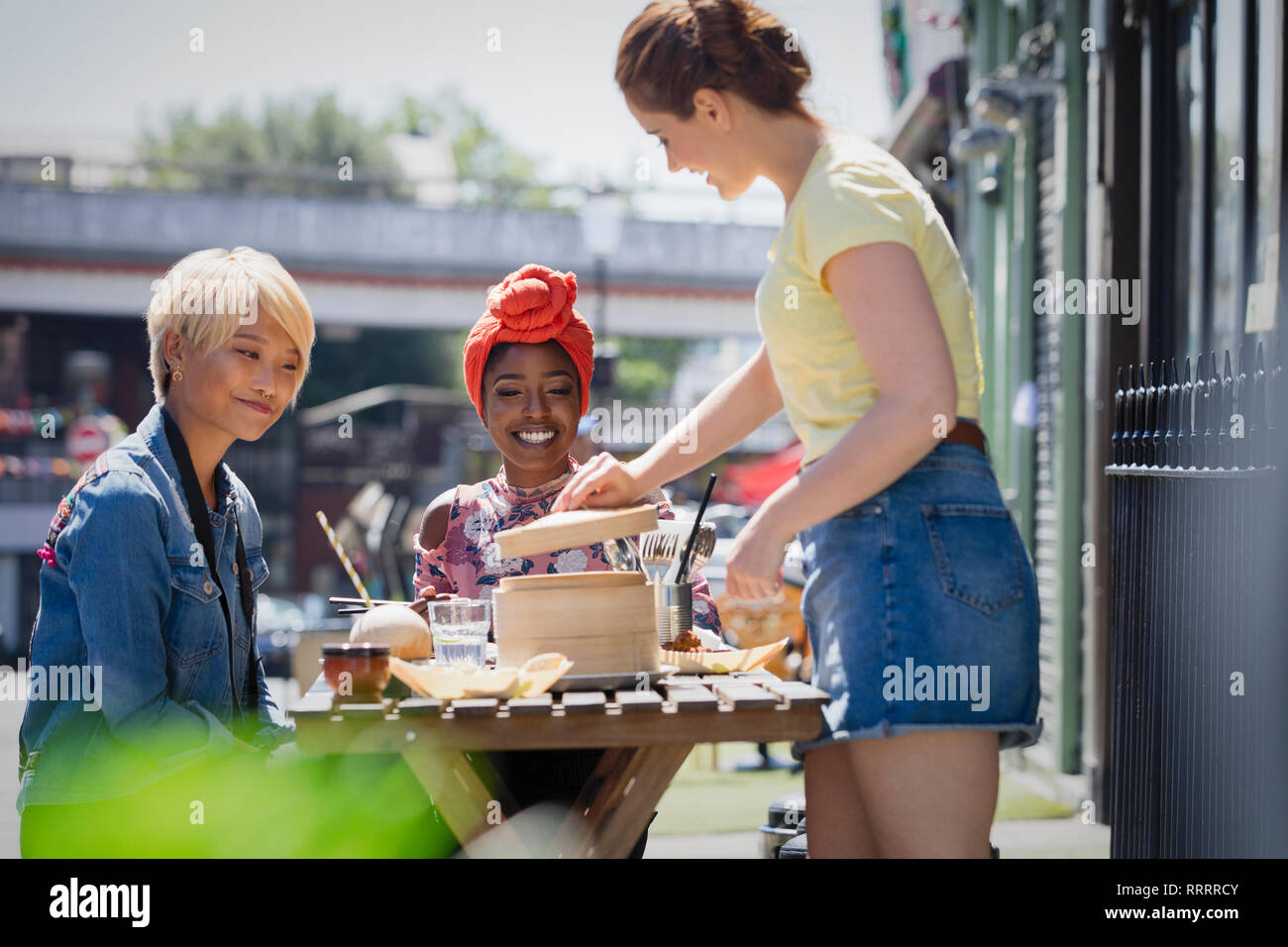 Young women friends enjoying dim sum lunch at sunny sidewalk cafe - Stock Image