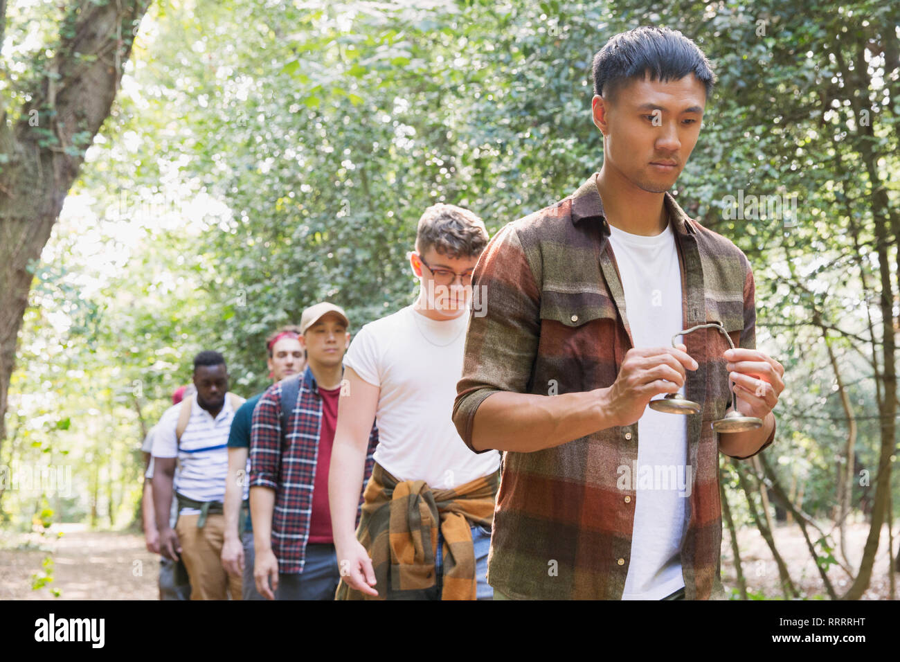 Man with tingsha cymbals leading mens group hike in woods - Stock Image