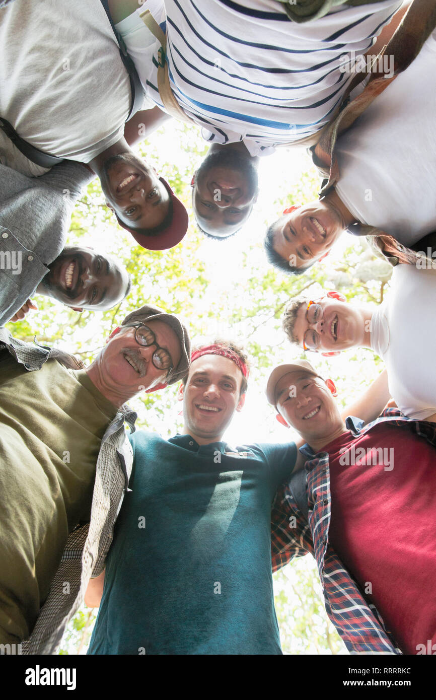 View from below mens group standing in huddle - Stock Image