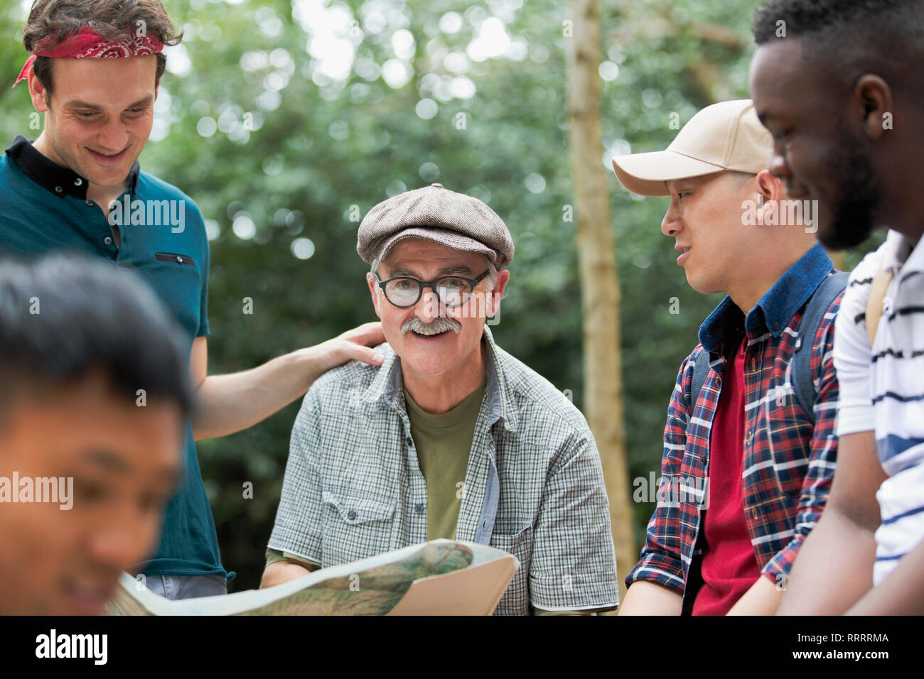 Portrait smiling man with map on hike with friends Stock Photo
