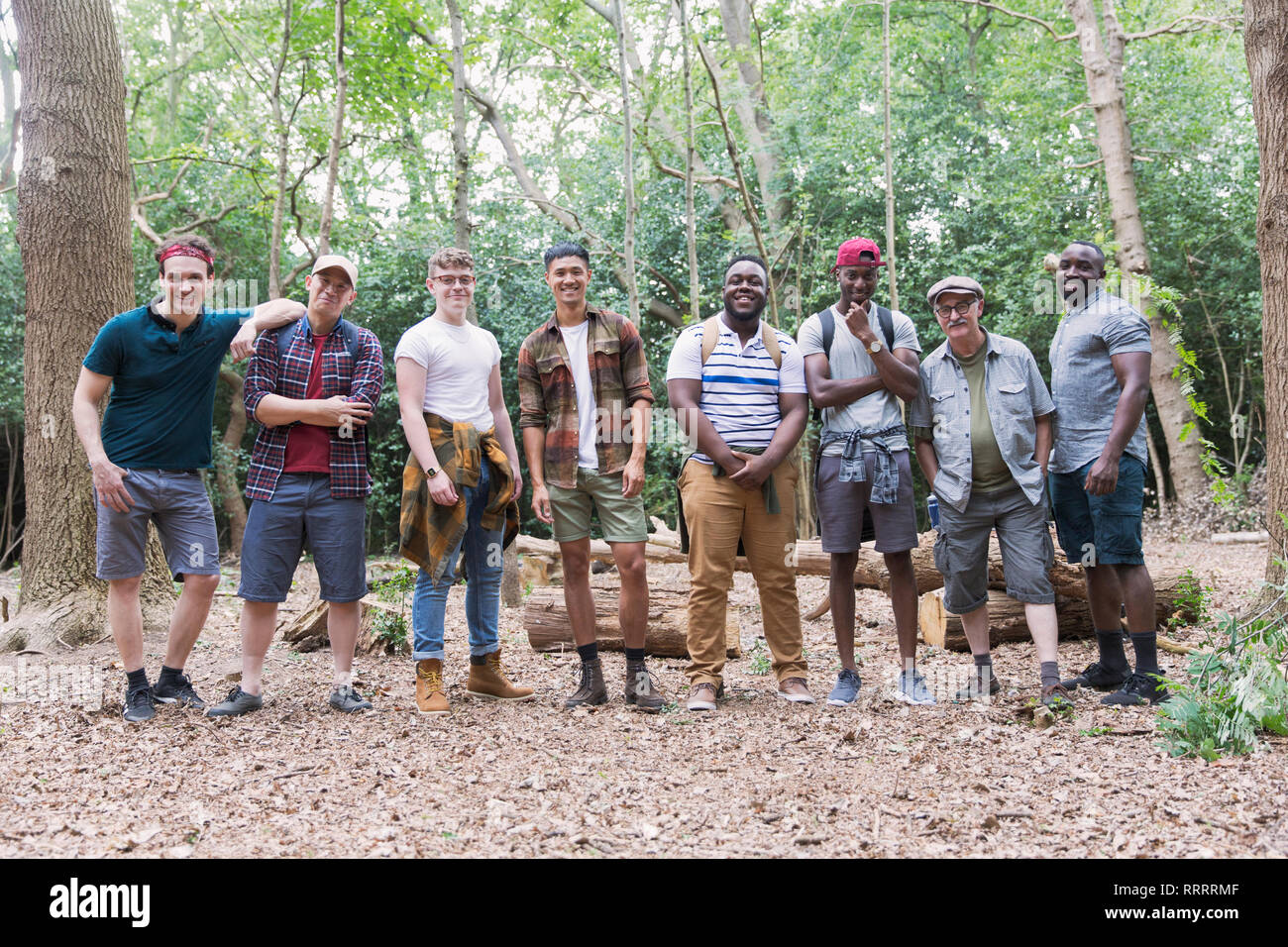 Portrait confident mens group hikers standing in a row in woods Stock Photo