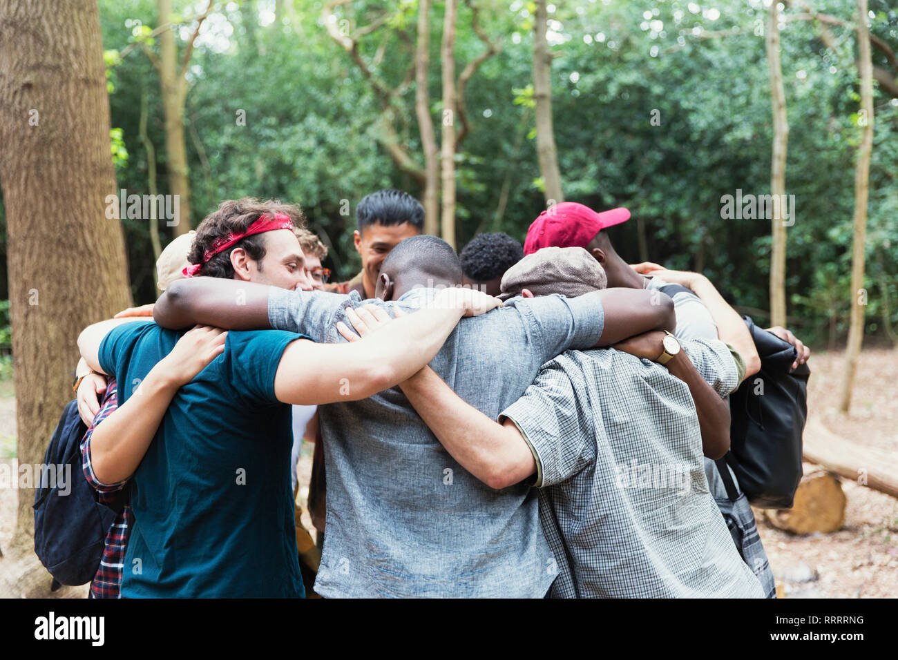 Men friends hugging in huddle on hike in woods Stock Photo