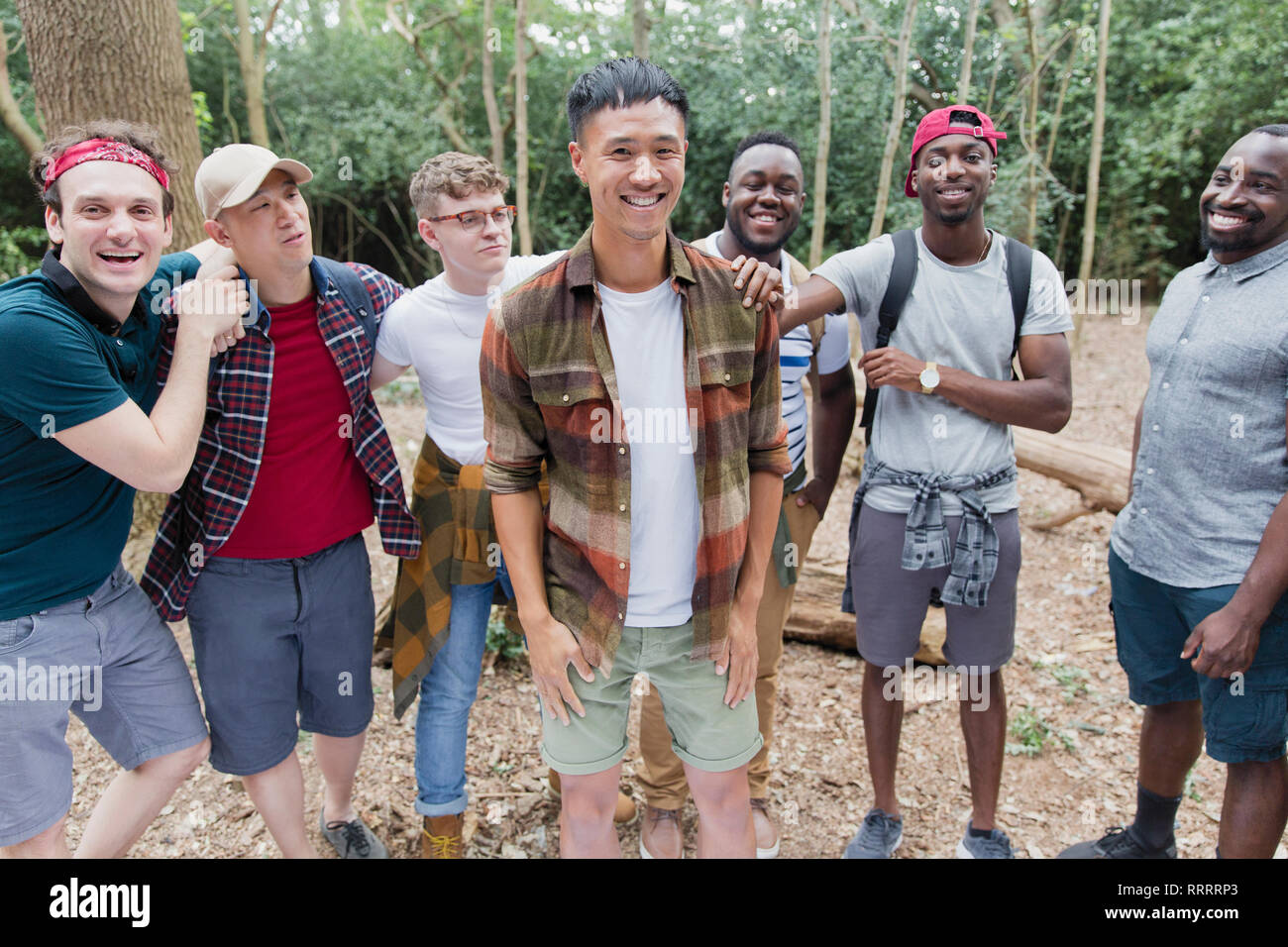Portrait happy, carefree mens group hiking in woods - Stock Image