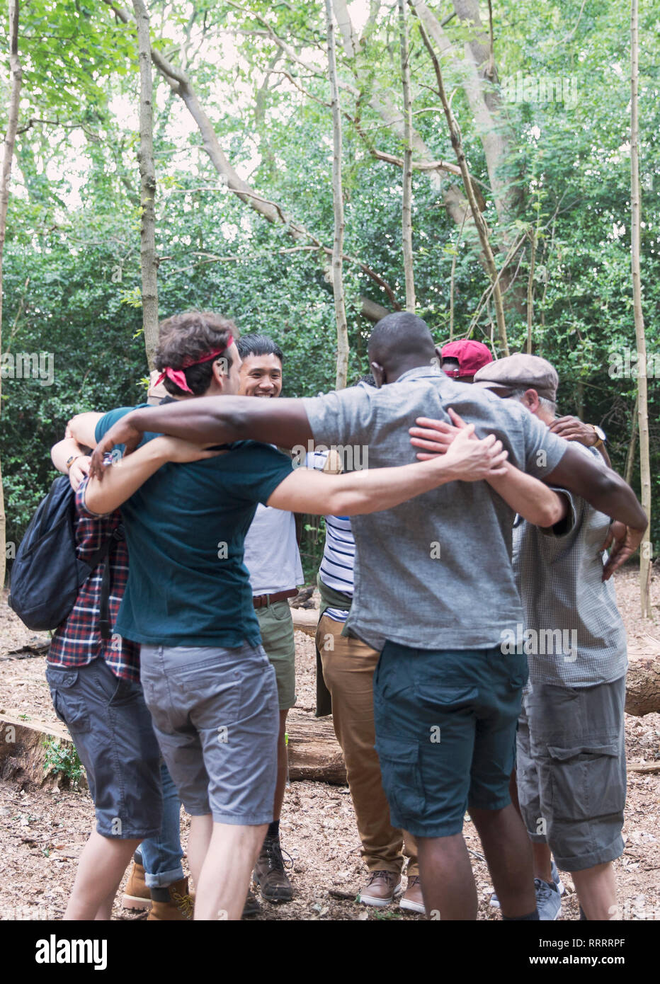 Mens group hugging in huddle, hiking in woods - Stock Image