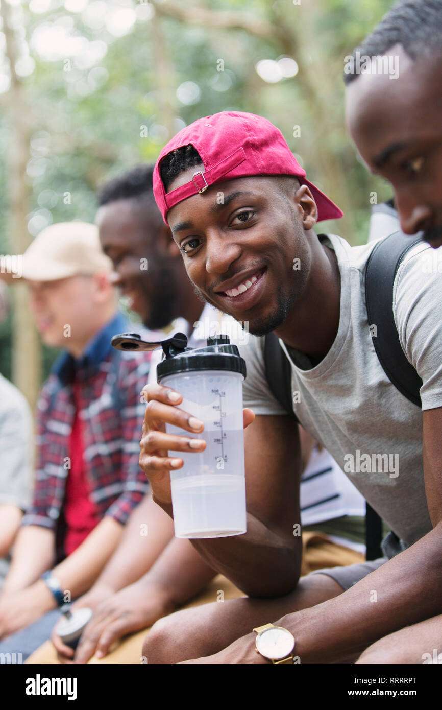 Portrait smiling man drinking water, preparing for hike Stock Photo