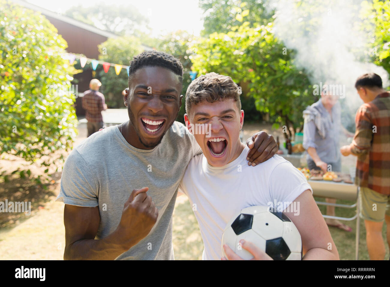 Portrait enthusiastic young men with soccer ball cheering, enjoying back yard barbecue - Stock Image