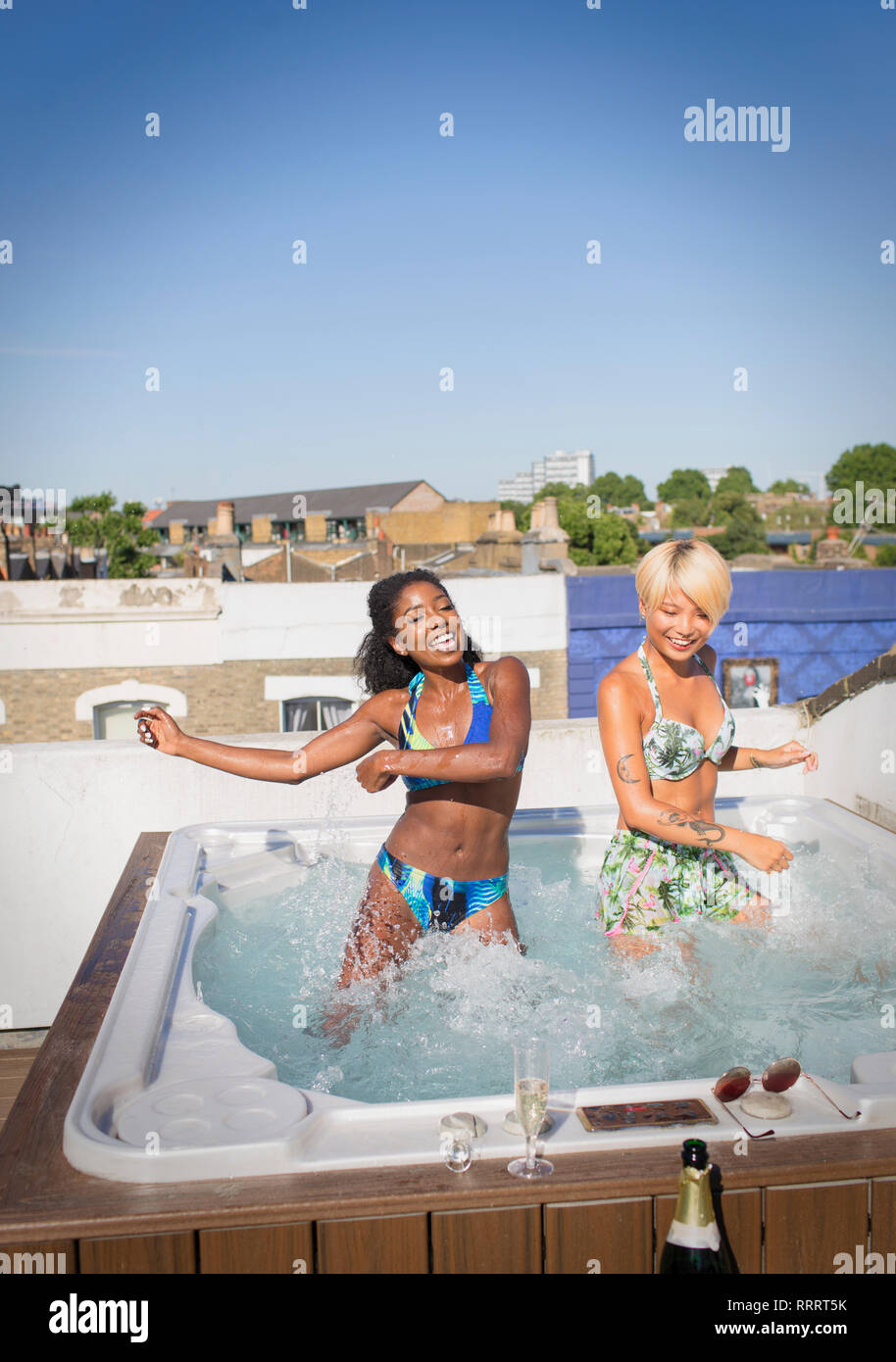 Playful young women friends in bikinis dancing in sunny rooftop hot tub - Stock Image