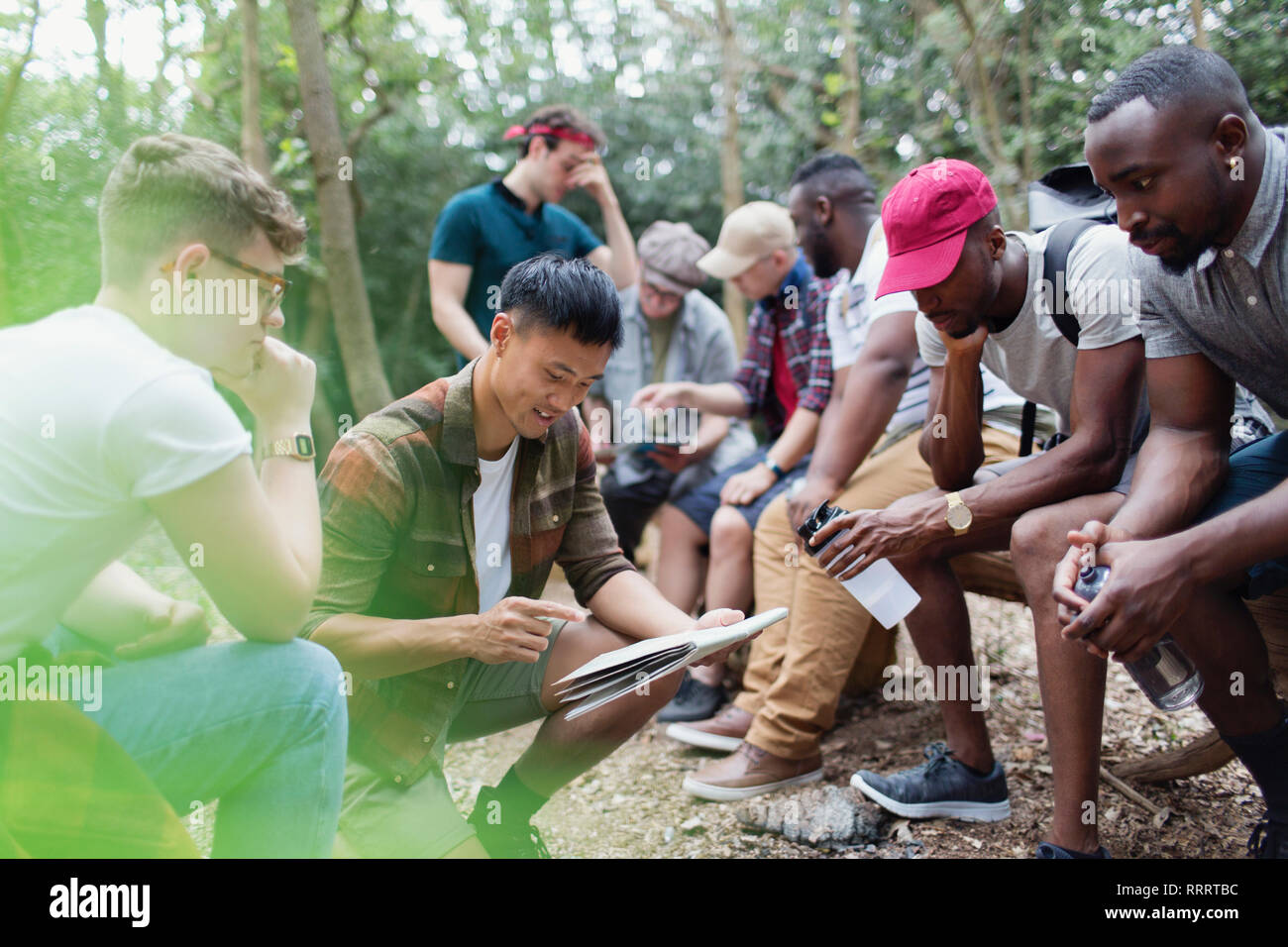 Mens group with map preparing for hike in woods - Stock Image