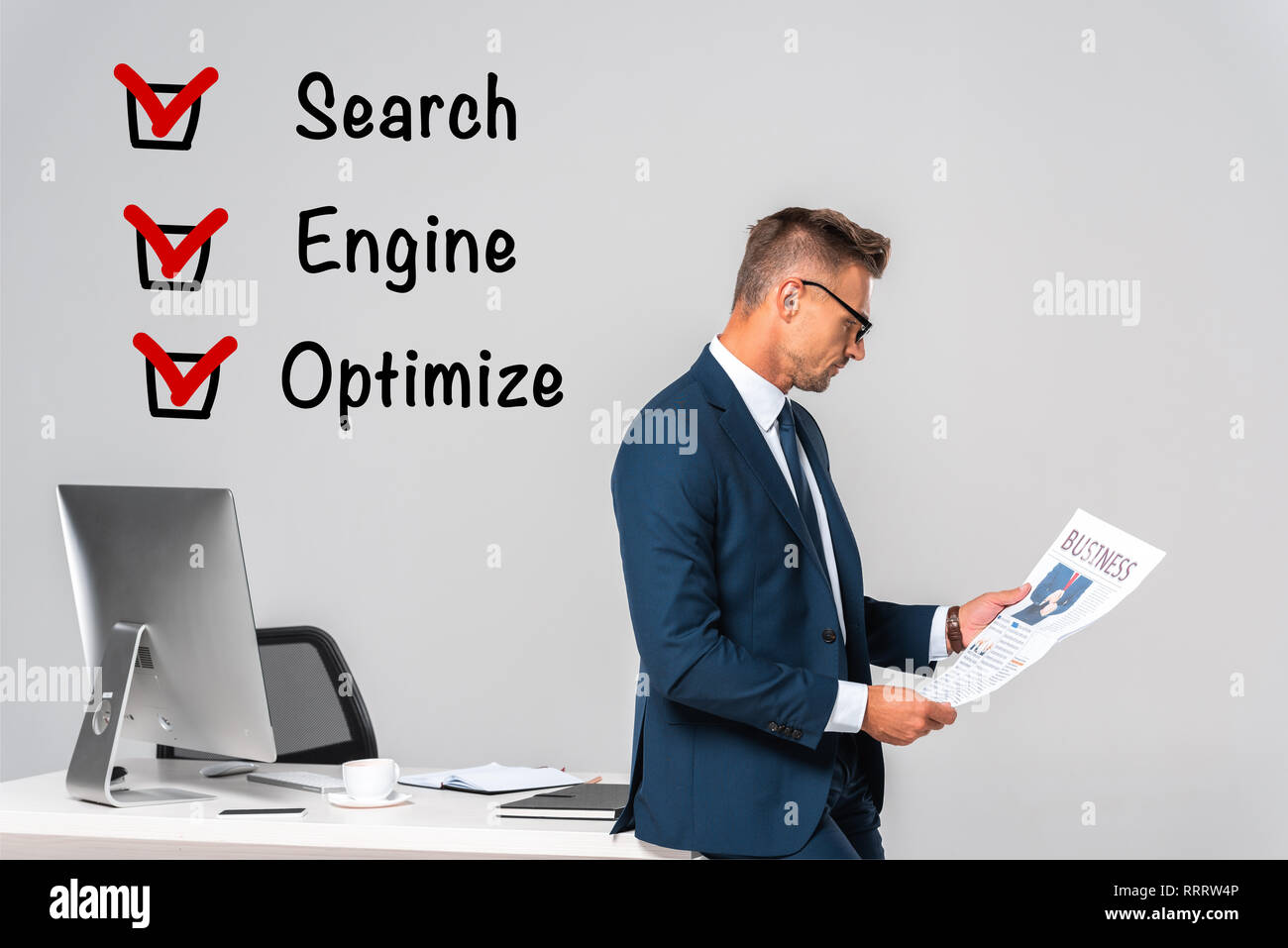 side view of handsome businessman reading newspaper isolated on grey with seo signs Stock Photo