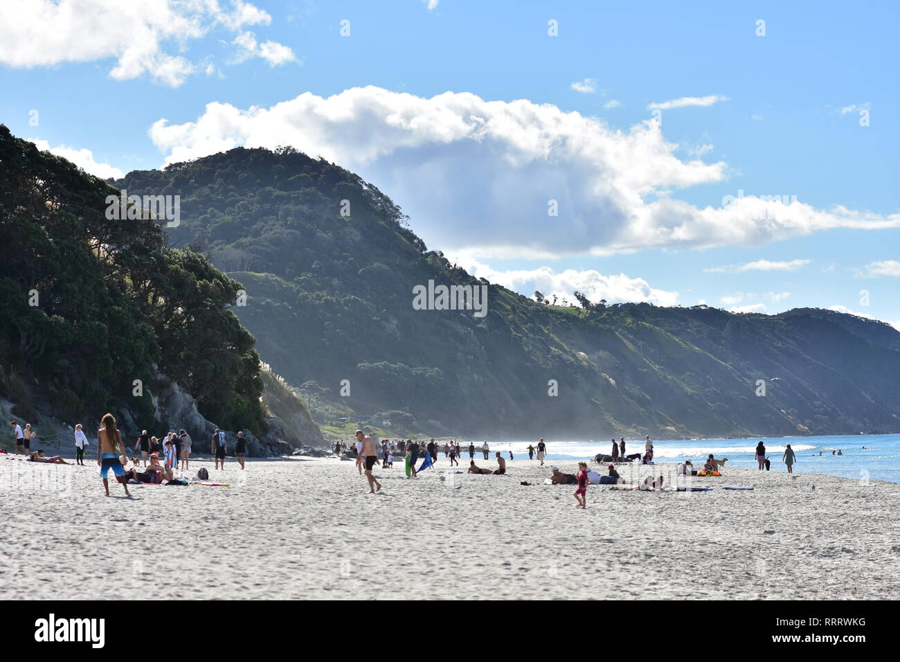 Crowds of people enjoying sunny day on flat sandy Pacific Ocean beach in Mangawhai Heads with steep hills in background. - Stock Image