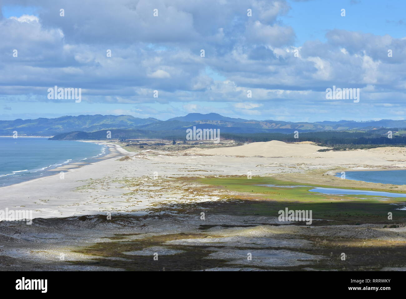 Sand dunes of various colors covered with native weeds forming barrier between calm harbor and open ocean. - Stock Image