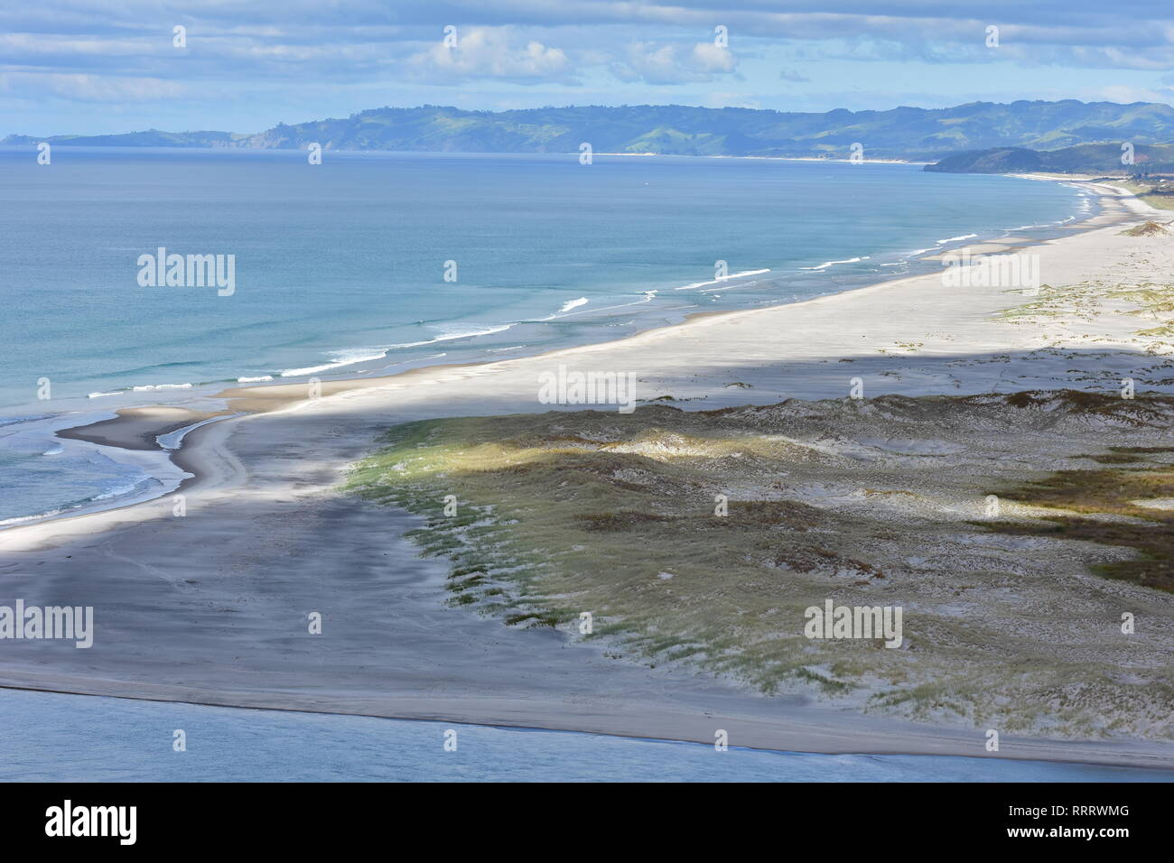 Flat tidal sandy coastal area partially shaded by clouds followed by dune covered with native weeds on coast of New Zealand Northland. - Stock Image