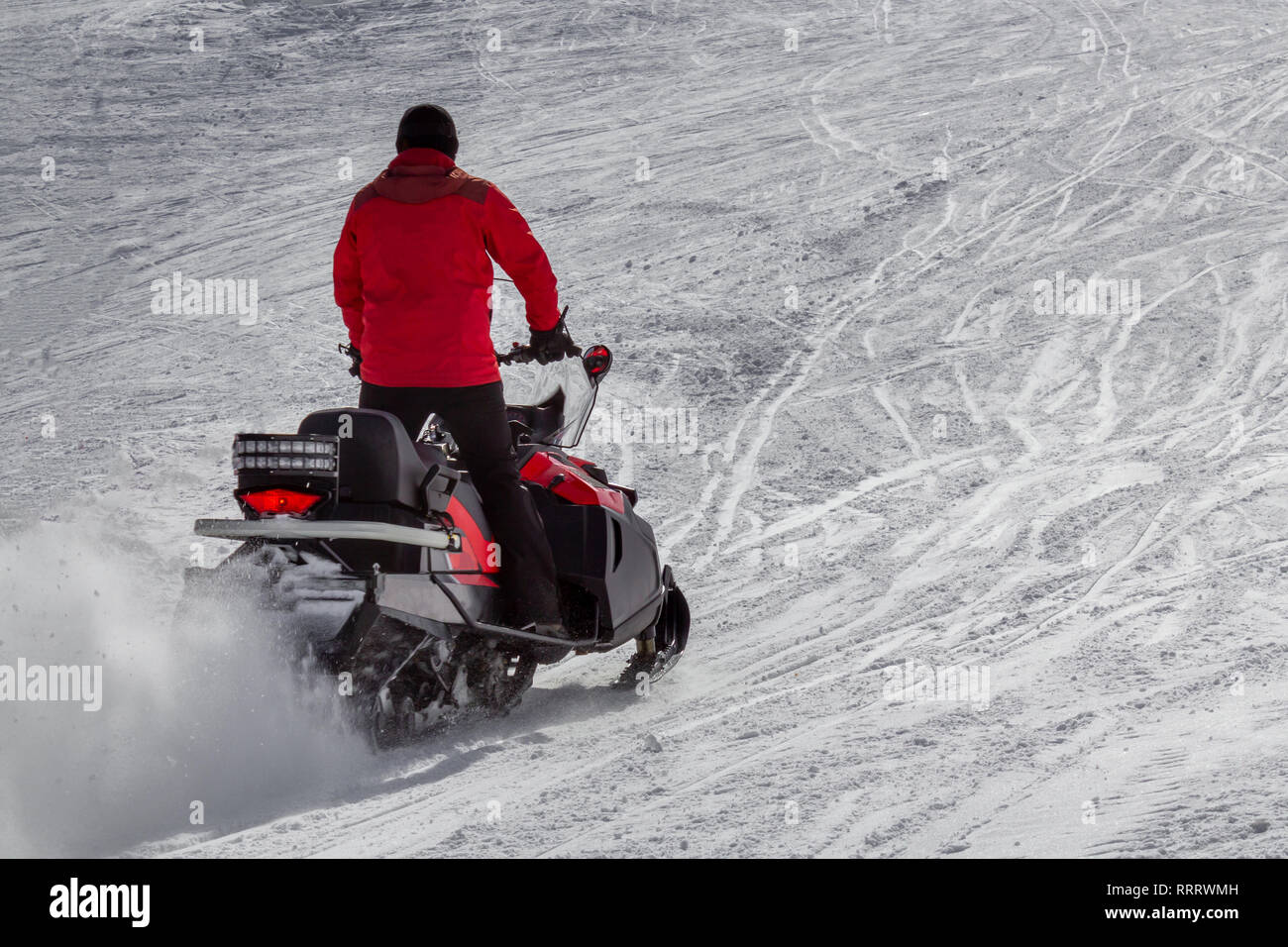 Man driving a snowmobile - Stock Image