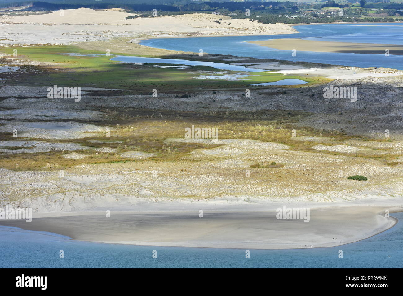 Flat sandy coast with dunes of various colors covered with weeds stretching from open coast to enclosed harbor. - Stock Image