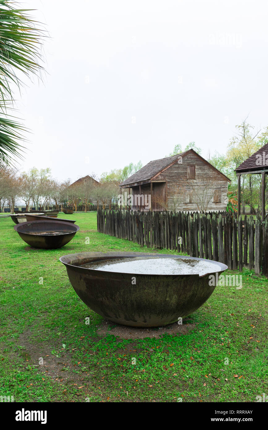 View of large iron bowls used by slaves for boiling down and refining sugar cane sited in the Whitney Plantation Museum in Louisiana, USA - Stock Image