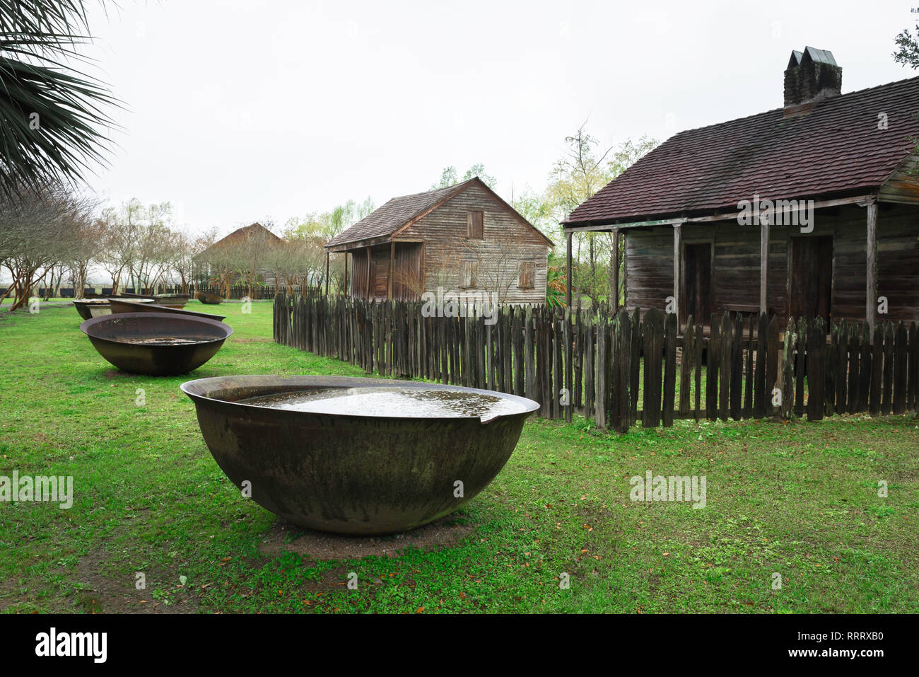 View of slave cabins with large iron bowls used for boiling down and refining sugar cane sited in the Whitney Plantation Museum in Louisiana, USA - Stock Image