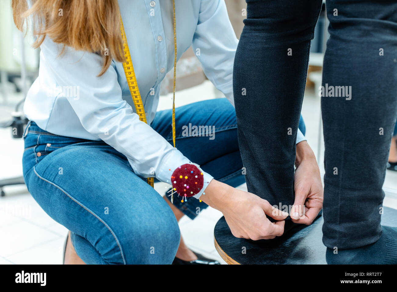 Alterations tailor measuring trousers on a customer - Stock Image