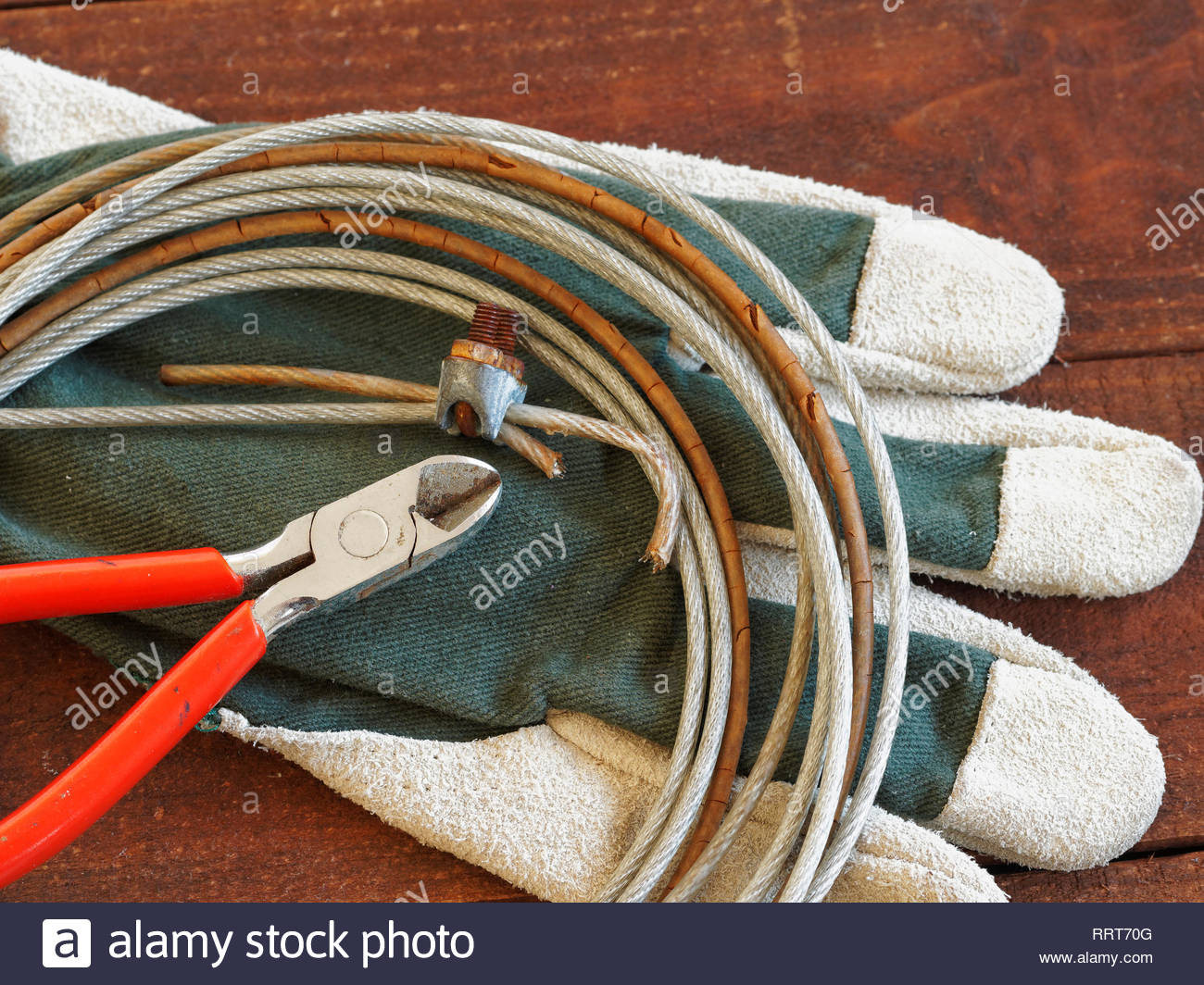 Wire cutters with work gloves and roll of rusty wire on dark wooden background Stock Photo