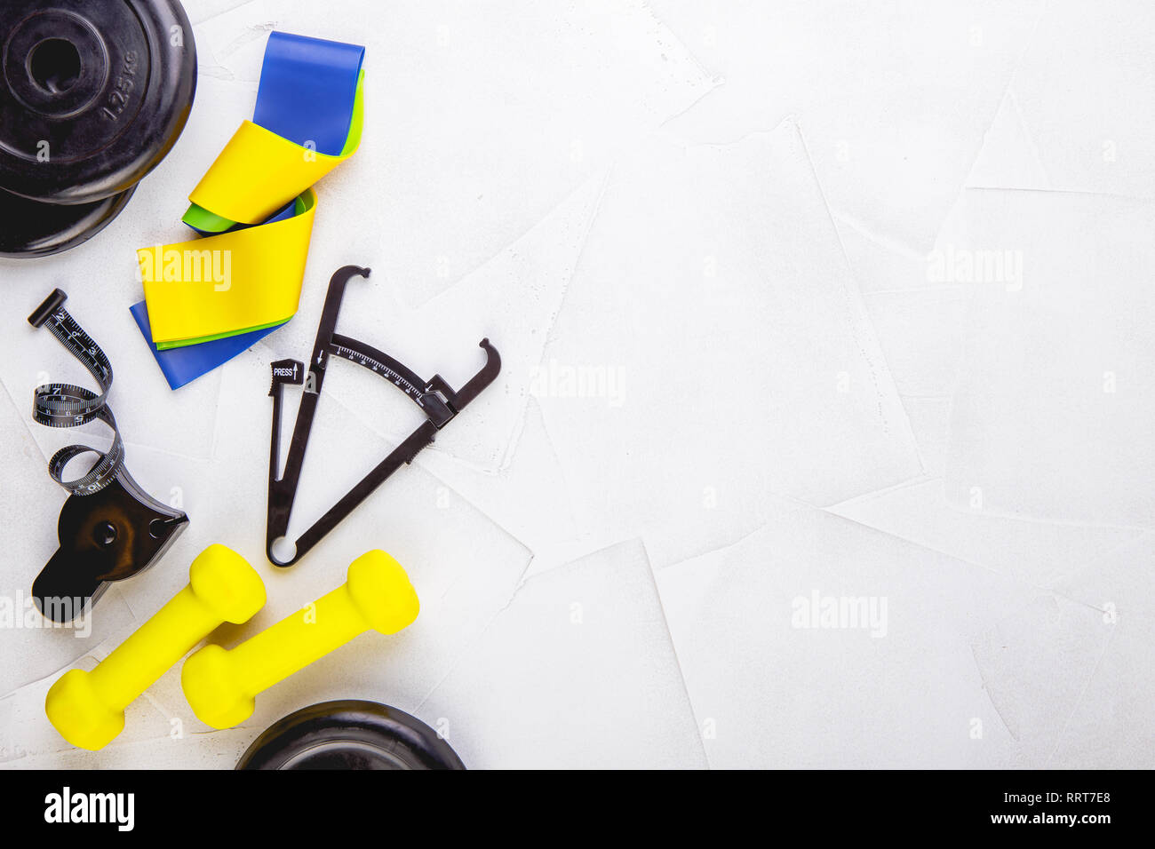 Top view image of dumbbells, colorful elastic gum expanders, calipers and measuring tape on a white textured background. Healthy lifestyle, Gym and wo - Stock Image
