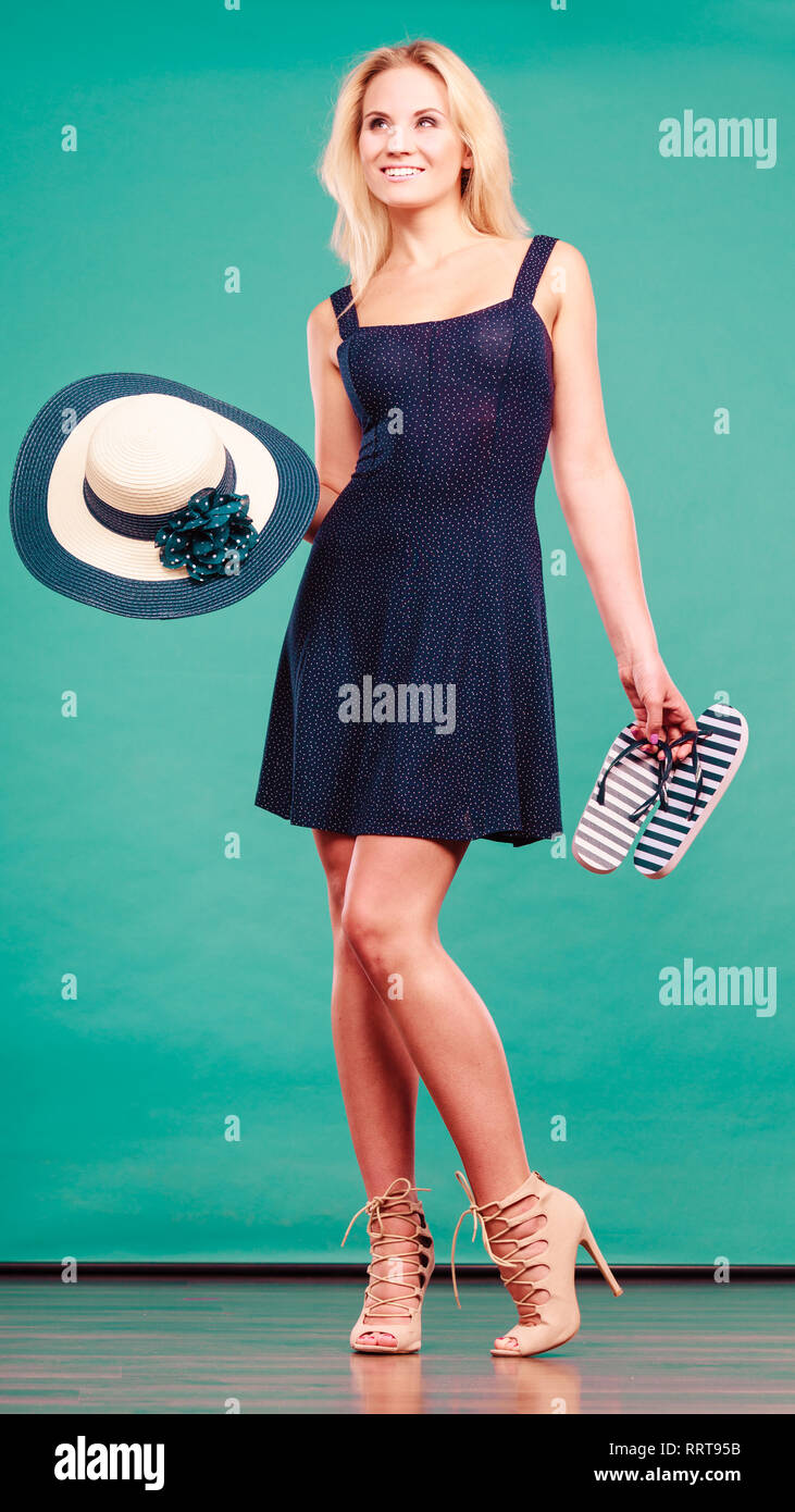 619ff5fceb57a Summer trendy fashionable outfit ideas concept. Woman wearing short navy  dress holding sun hat and