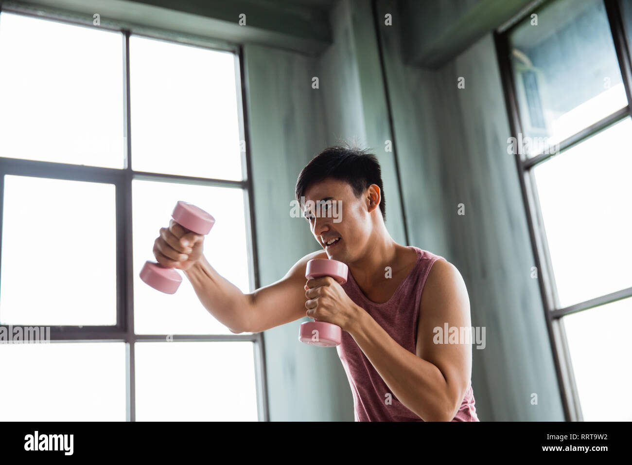 man using dumbbell doing some boxing exercise - Stock Image