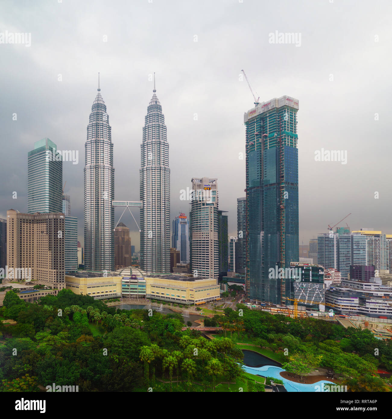 Petronas Twin Towers and the surrounding buildings in stormy weather with overcast sky - Stock Image