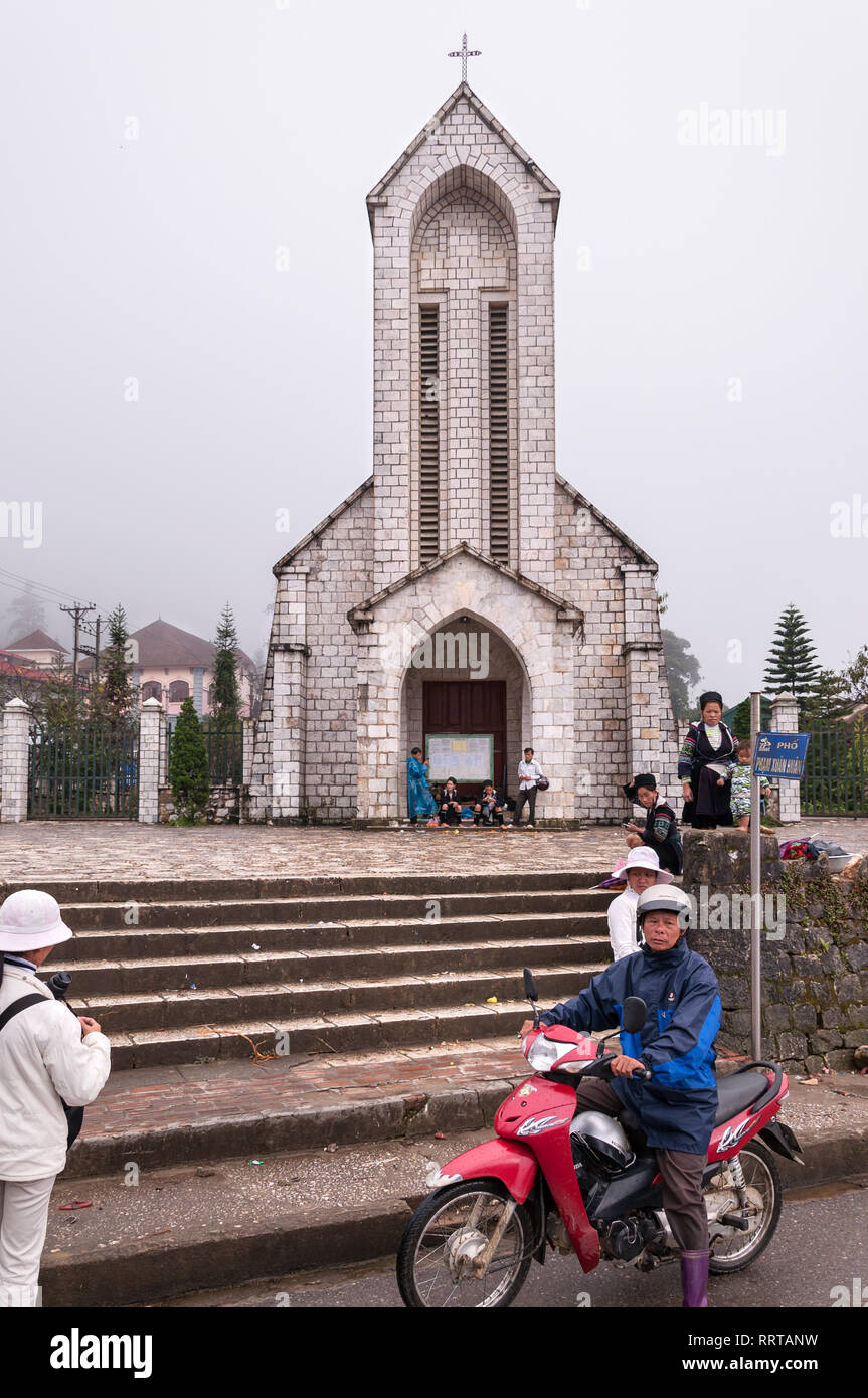 Nhà Thờ Đá Sapa or Notre Dame cathedral with local Vietnamese outside on an overcast day, Sa Pa, Vietnam Stock Photo