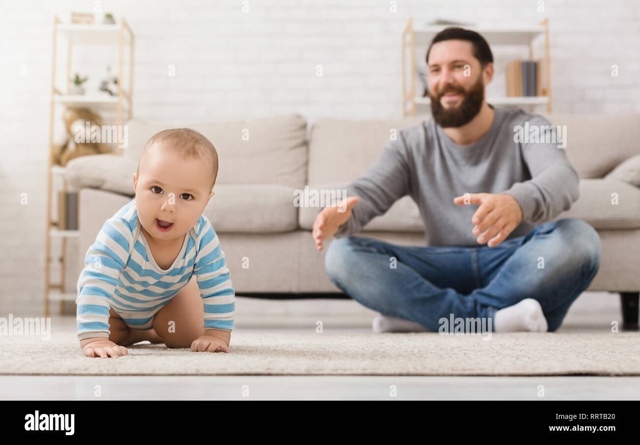 Adorable baby boy crawling on floor with dad - Stock Image