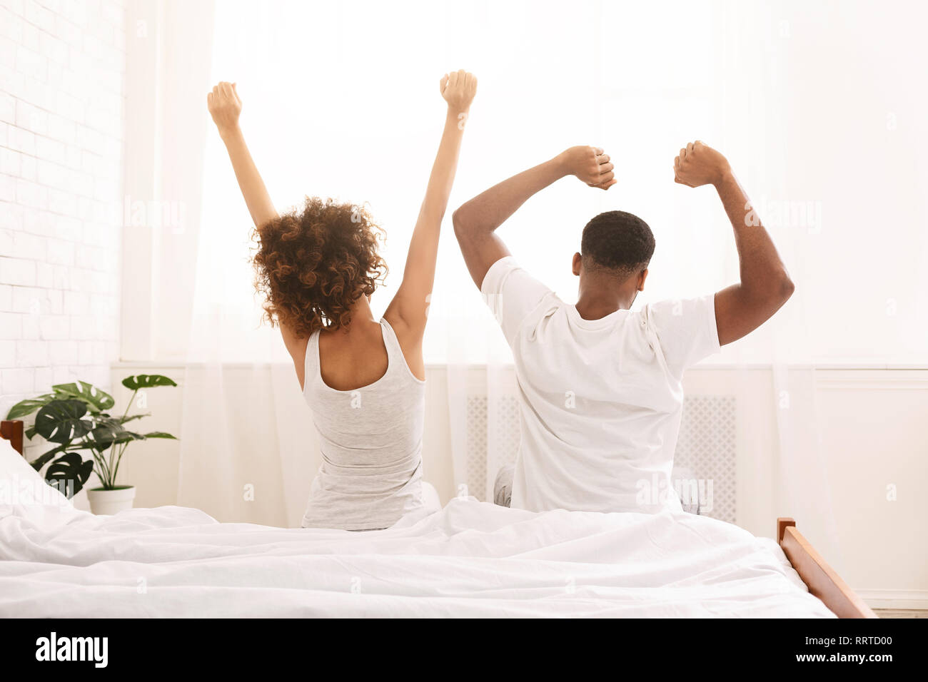 Funny married couple stretching in bedroom after wakeup - Stock Image